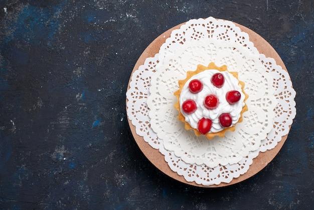 暗い表面のケーキフルーツの赤いフルーツとトップビューおいしいクリームケーキ