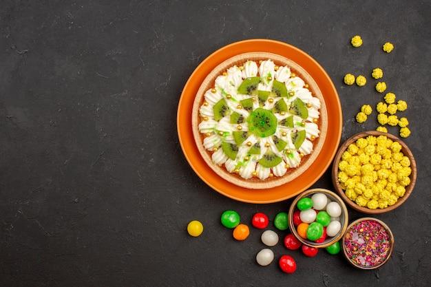 Vista dall'alto delizioso dessert alla crema con caramelle su sfondo scuro caramelle color crema biscotto