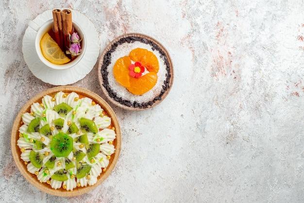 Вид сверху вкусного кремового десерта с чашкой чая на белом столе цветной конфеты бисквитный кремовый десерт