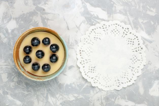 トップビューライトホワイトの表面に小さな鍋の中にブドウが上にあるおいしいクリームデザートアイスクリームデザートクリームスイート