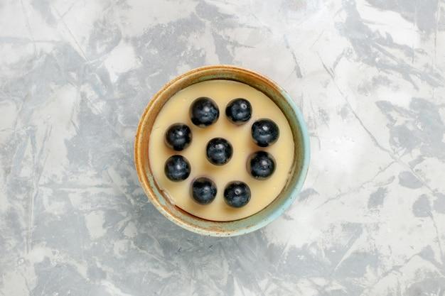 Vista dall'alto un delizioso dessert alla crema con l'uva in cima all'interno della piccola pentola sulla superficie bianca del gelato alla crema dolce