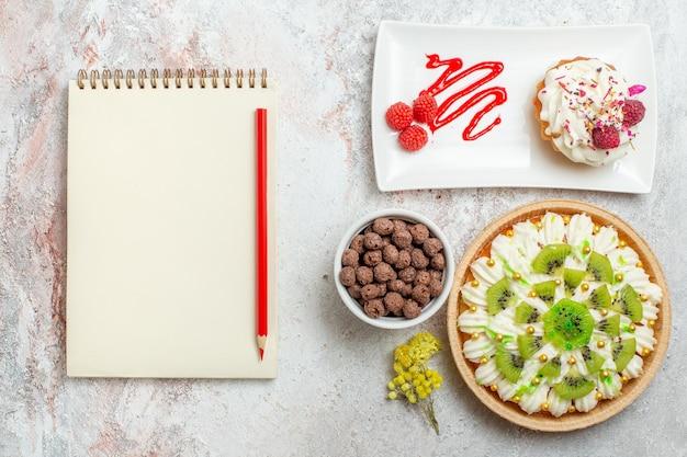 白い机の上の白いクリームとスライスしたキウイのトップビューおいしいクリームデザートカラーキャンディビスケットクリームデザート