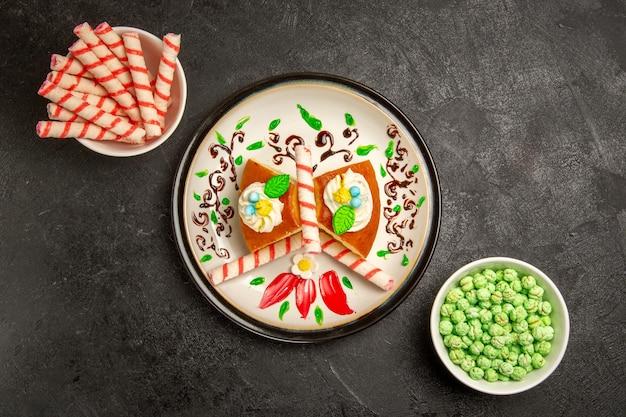 Vista dall'alto deliziosa torta alla crema all'interno di un piatto progettato con caramelle sullo sfondo scuro torta torta di crema di biscotto dolce