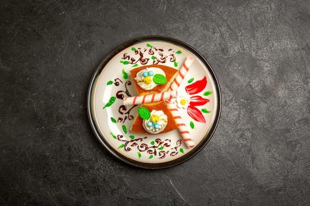 Вид сверху вкусный кремовый пирог, кусочки сладкого торта внутри тарелки на темном фоне, цвет пирога, сладкий бисквитный крем