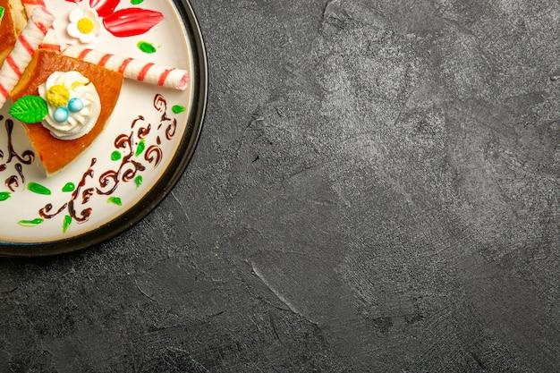 Вид сверху вкусного кремового пирога, кусочков сладкого торта внутри тарелки на темном фоне, цвета пирога, сладкого бисквитного крема