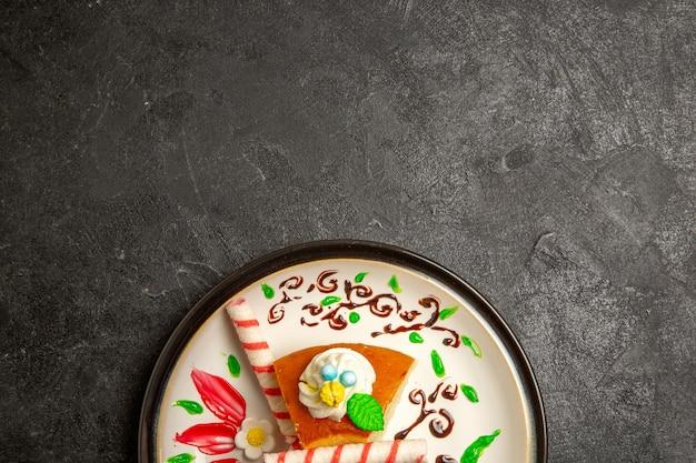 暗い机の上のデザインされたプレート内のおいしいクリームパイの甘いケーキのスライスの上面図ケーキパイの色の甘いビスケットクリーム