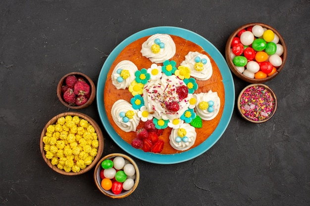 Top view delicious cream pie with fruits and candies on dark background pie cookie sweet biscuit cake tea