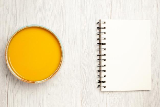 Vista dall'alto deliziosa zuppa di crema zuppa di colore giallo con blocco note sulla scrivania bianca zuppa di salsa pasto crema piatto cena