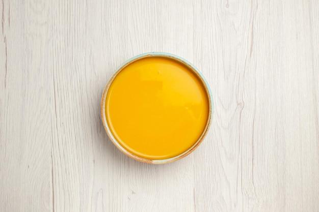 Vista dall'alto deliziosa zuppa di crema piatto giallo sulla scrivania bianca zuppa di salsa pasto crema piatto cena