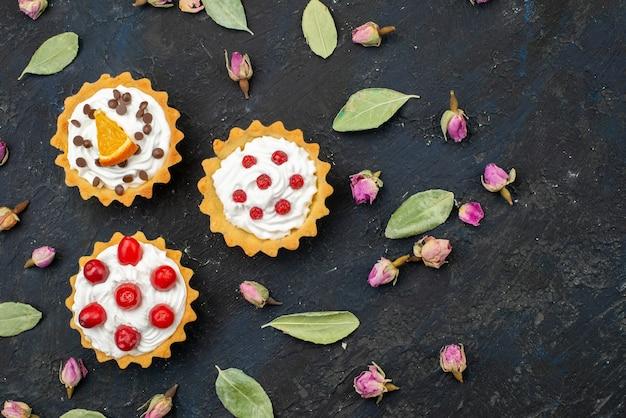Вид сверху вкусные кремовые пирожные с фруктами на вершине, изолированными на темном столе, сахарные сладкие фрукты
