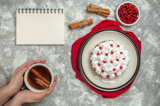 Top view of delicious creamy cake decorated with fruits on a red cloth