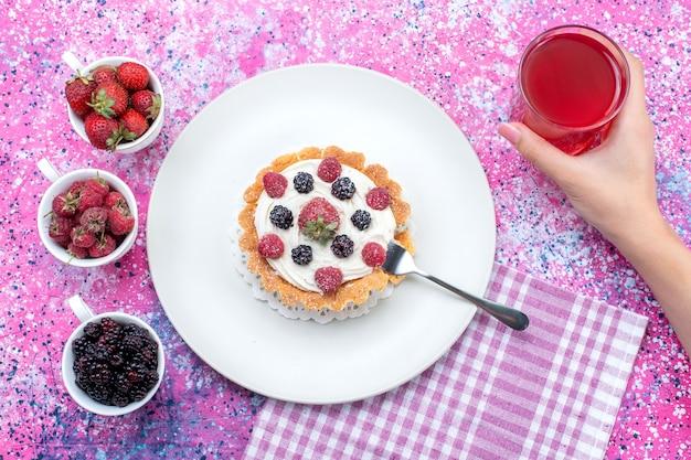 Vista dall'alto di una deliziosa torta cremosa con diversi succhi di frutti di bosco freschi su luce intensa, frutti di bosco freschi acidi