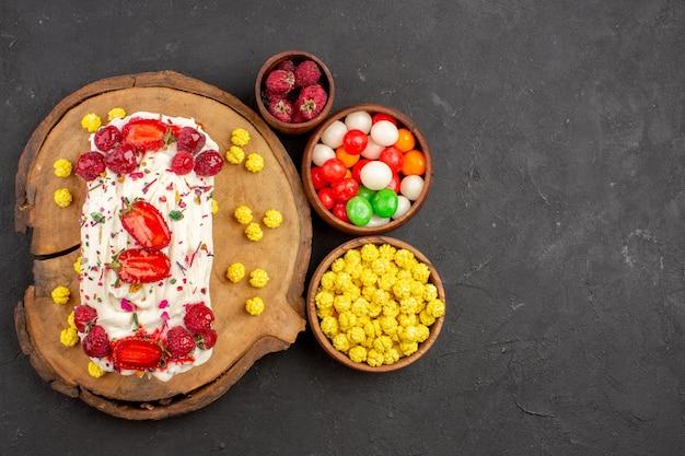 トップビュー暗い背景に果物やキャンディーとおいしいクリーミーなケーキビスケットティークッキーケーキ甘いクリーム