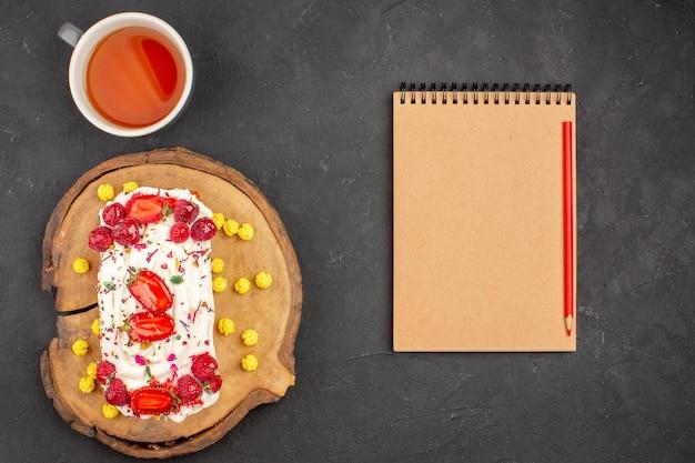 Vista dall'alto deliziosa torta cremosa con frutta e tazza di tè su sfondo scuro biscotti biscotti torta torta di crema di tè dolce sweet
