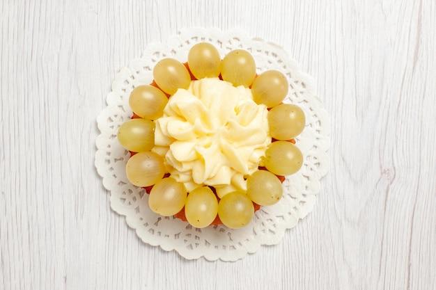 흰색 책상 과일 크림 케이크 비스킷 쿠키에 녹색 포도를 곁들인 맛있는 크림 케이크