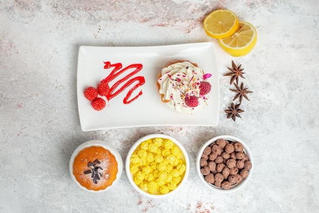 上面図白い背景の上のレモンとキャンディーとおいしいクリーミーなケーキビスケットクリームケーキティーキャンディー