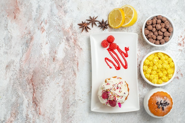 Top view delicious creamy cake with lemon and candies on white background biscuit cream cake tea candy