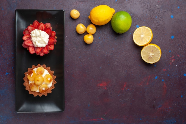 Vista dall'alto di deliziose torte cremose all'interno del piatto con limoni freschi sulla superficie scura