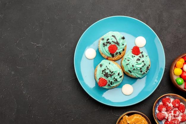 Vista dall'alto deliziose torte cremose con caramelle sulla scrivania scura torta dessert biscotto caramelle biscotti colore