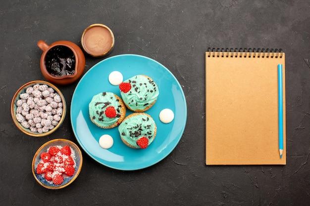 トップビュー暗い背景にキャンディーとおいしいクリーミーなケーキデザートケーキビスケットキャンディークッキーの色