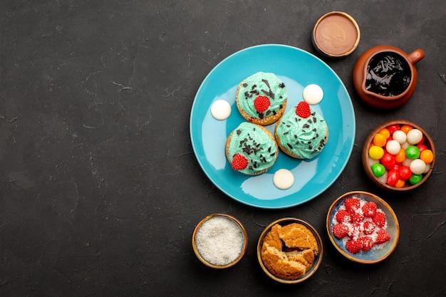 トップビュー暗い背景にキャンディーとおいしいクリーミーなケーキビスケットケーキデザートキャンディークッキーの色