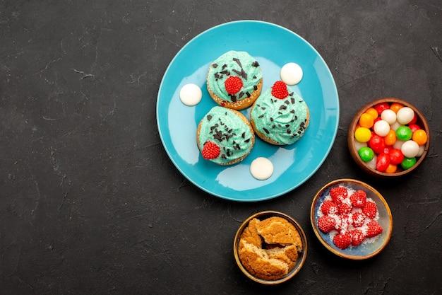 暗い背景の上のキャンディーとおいしいクリーミーなケーキの上面図ケーキデザートビスケットキャンディークッキーの色