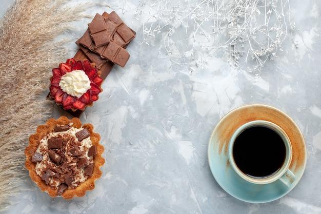 Вид сверху вкусные сливочные пирожные с шоколадными батончиками и чаем на белом столе, бисквитный торт, сладкая сахарная выпечка