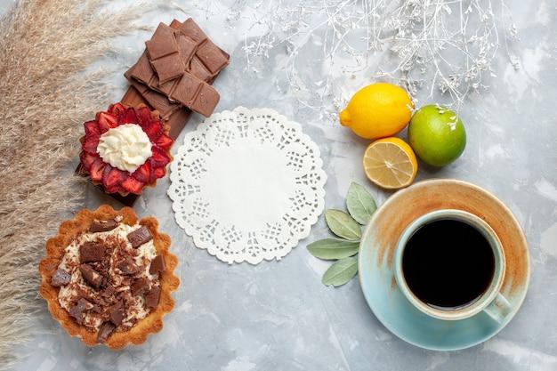 Vista dall'alto deliziose torte cremose con barrette di cioccolato limoni sulla scrivania bianca torta biscotto zucchero dolce cuocere
