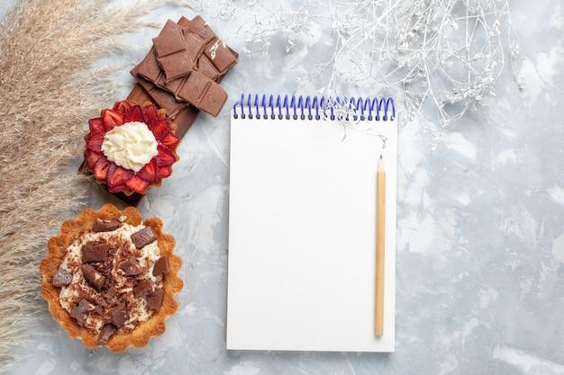 Vista dall'alto deliziose torte cremose con barrette di cioccolato sulla scrivania bianca torta biscotto dolce cuocere