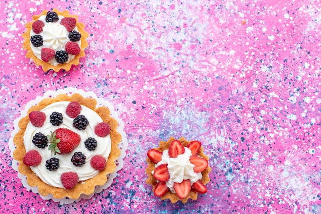 Top view of delicious creamy cakes with different berries on purple bright, fruit berry cake biscuit bake