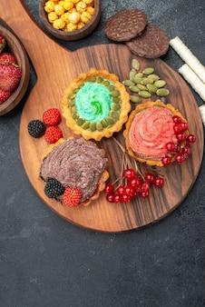 Vista dall'alto deliziose torte cremose con frutta sui biscotti di biscotto dolce tavolo scuro