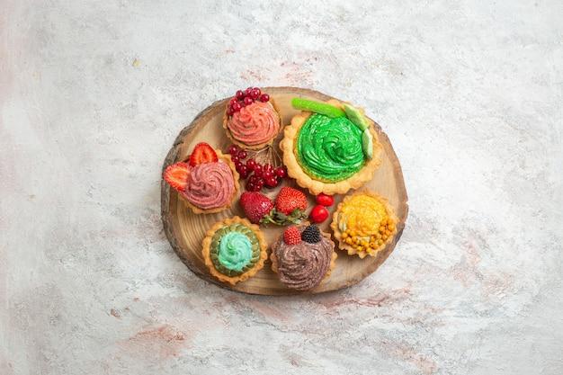 Vista dall'alto deliziose torte cremose con frutta su un dolce da dessert torta da tavolo bianco