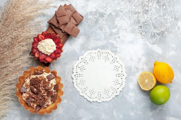 Vista dall'alto deliziose torte cremose con limone e barrette di cioccolato sulla scrivania bianca torta biscotto zucchero dolce cuocere