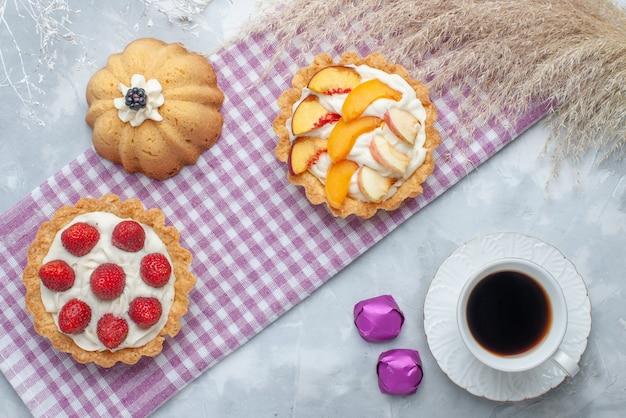 Vista dall'alto di deliziose torte cremose con frutta a fette insieme a caramelle al cioccolato e tè sulla scrivania luminosa, torta biscotto crema dolce cuocere zucchero per il tè