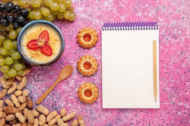 淡いピンクの背景に新鮮なブドウとピーナッツを添えたトップビューのおいしいクリーミーなデザートデザートアイスクリームベリークリームスイートフルーツ