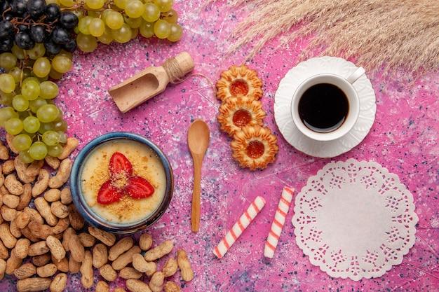 Вид сверху вкусный сливочный десерт со свежим виноградным печеньем и арахисом на светло-розовой поверхности десертное мороженое ягодный крем сладкие фрукты