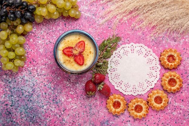 淡いピンクの背景に新鮮な緑のブドウとクッキーを添えたトップビューのおいしいクリーミーなデザートデザートアイスクリームベリークリーム甘い果物