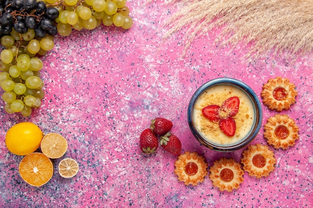 淡いピンクのデスクデザートアイスクリームベリークリームスイートフルーツに新鮮な緑のブドウとクッキーを添えたトップビューのおいしいクリーミーなデザート