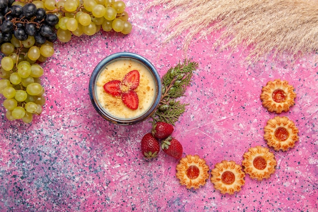 淡いピンクの背景に新鮮な緑のブドウとクッキーを添えたトップビューのおいしいクリーミーなデザートデザートアイスクリームベリークリームスイートフルーツ