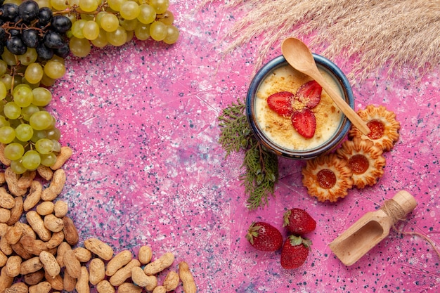 Вид сверху вкусный сливочный десерт со свежим зеленым виноградом, печенье и арахис на светло-розовом фоне десертное мороженое ягодный крем сладкие фрукты