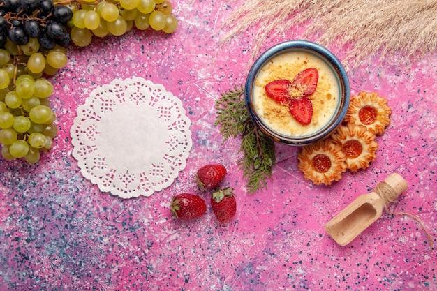 Vista dall'alto delizioso dessert cremoso con uva verde fresca e biscotti sullo sfondo rosa chiaro dessert gelato alla crema di frutti di bosco dolce frutta