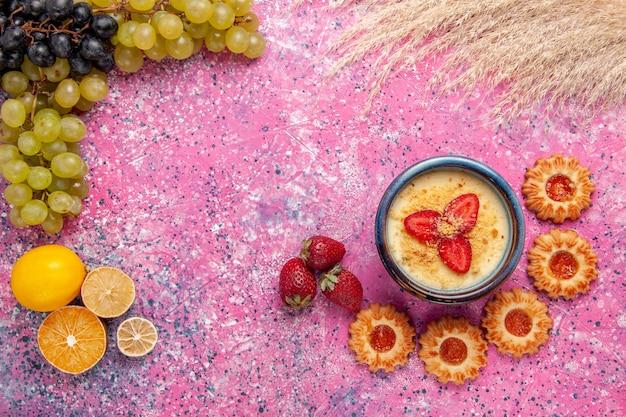 Vista dall'alto delizioso dessert cremoso con uva verde fresca e biscotti sulla frutta dolce crema di bacche di gelato da tavolo rosa chiaro