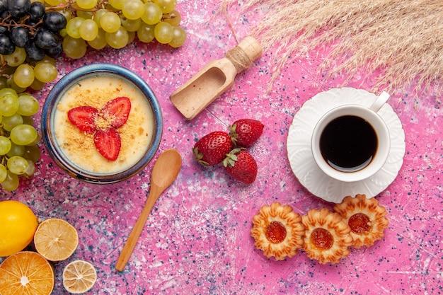 Vista dall'alto delizioso dessert cremoso con uva verde fresca tazza di tè e biscotti sulla superficie rosa chiaro dessert gelato alla crema di bacche frutta dolce