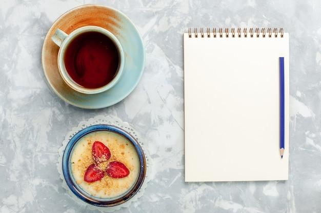 新鮮なイチゴのメモ帳と水色の背景にお茶を添えたトップビューのおいしいクリーミーなデザートデザートアイスクリーム甘いフルーツの味