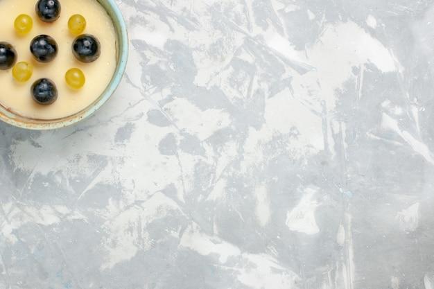 平面図ライトホワイトの表面の小さな鍋の中に果物が上にあるおいしいクリーミーなデザートフルーツクリームデザートアイスクリームスイートアイス