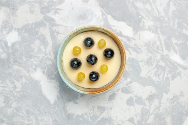 上面図白い背景の小さな鍋の中に果物が上にあるおいしいクリーミーなデザートフルーツクリームデザートアイスクリームスイートアイス