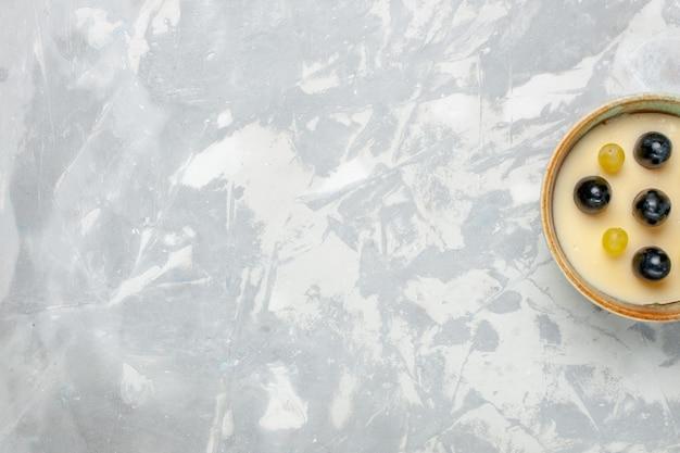 上面図白い背景の上の小さな鍋の中に果物が上にあるおいしいクリーミーなデザートフルーツクリームデザートアイスクリーム甘い氷