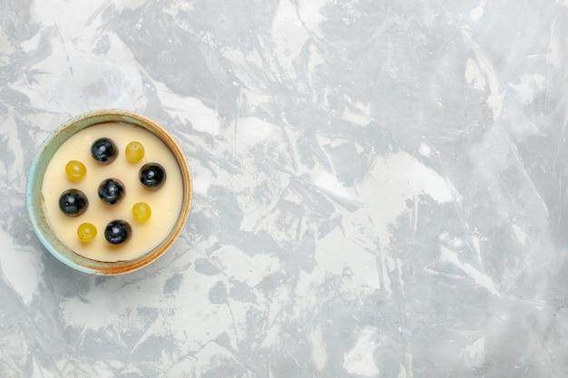 Vista dall'alto delizioso dessert cremoso con frutta in cima all'interno di una piccola pentola sulla superficie bianca crema di frutta dessert gelato gelato dolce
