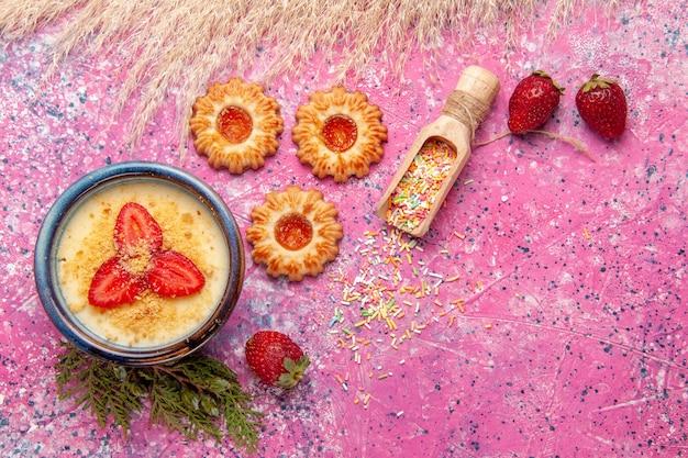 라이트 핑크 데스크 디저트 아이스크림 크림 달콤한 베리 과일에 빨간색 슬라이스 딸기와 쿠키가있는 상위 뷰 맛있는 크림 디저트