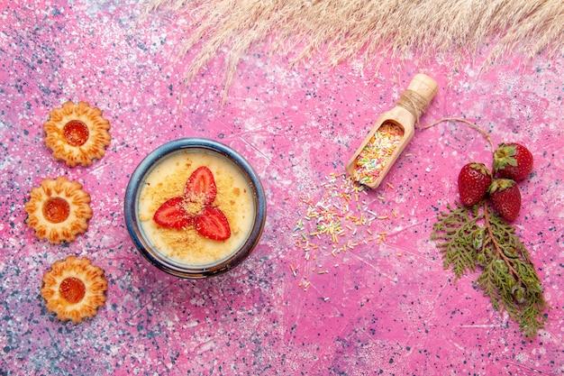 トップビューライトピンクの背景に赤いスライスしたイチゴとクッキーのおいしいクリーミーなデザートデザートアイスクリームベリークリーム甘いフルーツ